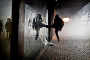 A-protestor-kicks-the-glass-of-a-commercial-center-during-the-general-strike-clashes-between-protestors-and-police-in-Barcelona-Spain.-Juanfra-Alvarez-960x640