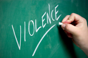 "A hand writes the word ""Violence"" on a chalkboard."